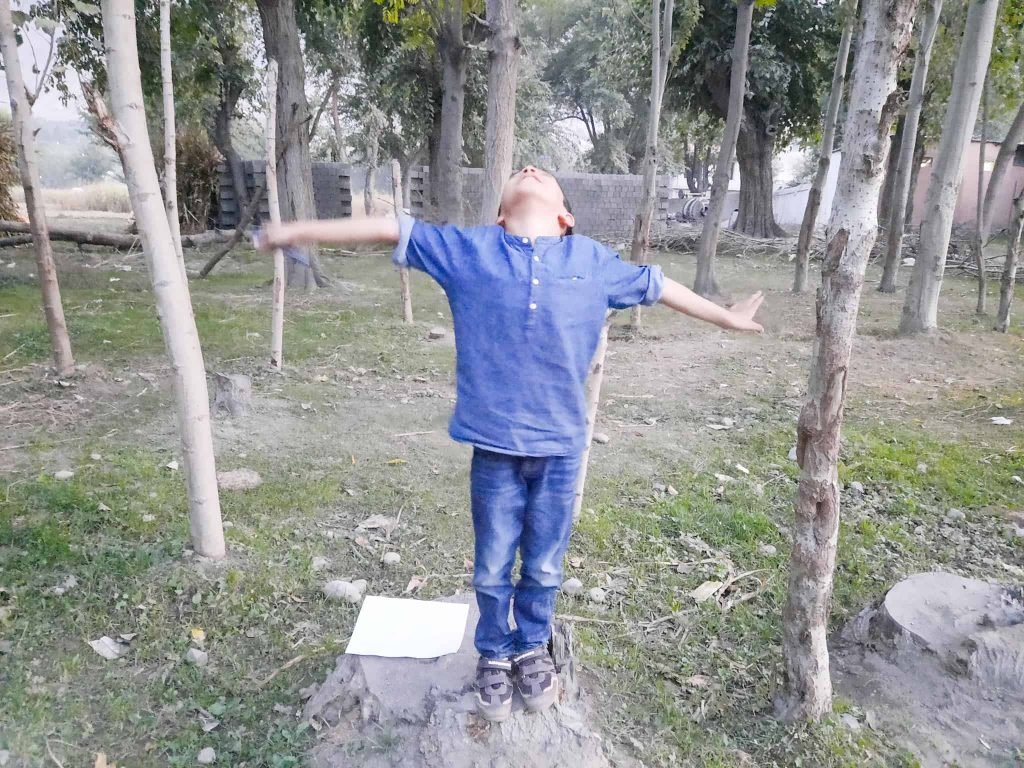 child standing on a tree stump with arms open to pretend he is the rest of the tree, while the fall scavenger hunt printable lies on the stump by the child's feet